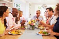Amis mûrs s'asseyant autour du Tableau au dîner Image libre de droits