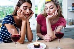 Amis malheureux s'asseyant à la table pendant la fête d'anniversaire Image libre de droits