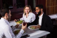 Amis mangeant à la table et à la causerie de restaurant Images stock