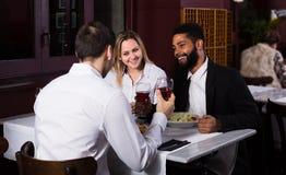 Amis mangeant à la table et à la causerie de restaurant Photographie stock libre de droits