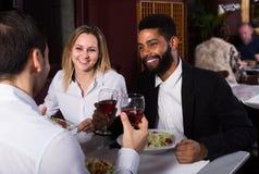 Amis mangeant à la table et à la causerie de restaurant Images libres de droits