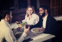 Amis mangeant à la table et à la causerie de restaurant Photos stock