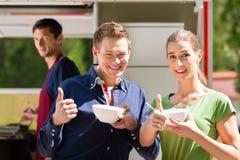 Amis mangeant d'une soupe sur la stalle de nourriture Photographie stock