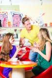 Amis mangeant de la glace en café Photographie stock
