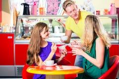 Amis mangeant de la glace en café Photos stock