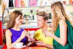 Amis mangeant de la glace en café Photos libres de droits