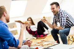 Amis mangeant de la pizza Photos stock