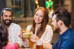 Amis mangeant de la pizza avec de la bière au restaurant Images libres de droits