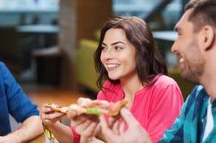 Amis mangeant de la pizza avec de la bière au restaurant Photos stock