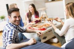 Amis mangeant de la pizza dans la chambre de Th Images libres de droits