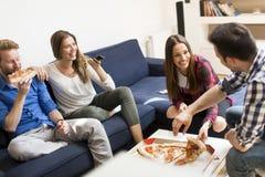 Amis mangeant de la pizza dans la chambre de Th Image libre de droits