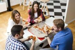 Amis mangeant de la pizza dans la chambre de Th Photos libres de droits