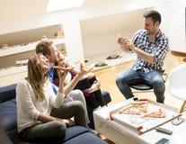 Amis mangeant de la pizza ensemble à la maison Image stock
