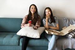 Amis mangeant de la pizza ensemble à la maison Photos libres de droits
