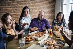 Amis mangeant de la pizza ensemble à la maison Images libres de droits