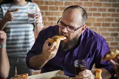 Amis mangeant de la pizza ensemble à la maison Photographie stock libre de droits