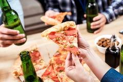 Amis mangeant de la pizza ensemble Photo stock