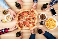 Amis mangeant de la pizza ensemble Images libres de droits