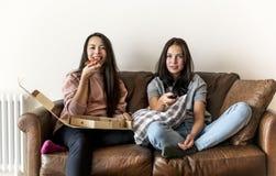 Amis mangeant de la pizza ensemble sur le divan Images stock