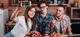 Amis mangeant de la pizza et prenant le selfie à la partie Image libre de droits