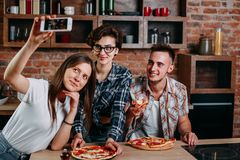 Amis mangeant de la pizza et prenant le selfie à la partie Photographie stock libre de droits