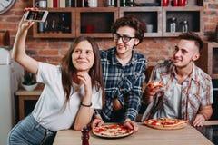 Amis mangeant de la pizza et prenant le selfie à la partie Images stock