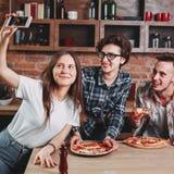 Amis mangeant de la pizza et prenant le selfie à la partie Image stock