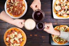Amis mangeant de la pizza Vue supérieure sur les mains masculines faisant tinter des tasses de bière Photos stock
