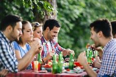 Amis mangeant dehors et ayant l'amusement Photo libre de droits