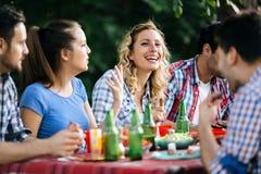 Amis mangeant dehors et ayant l'amusement Image libre de droits