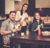 Amis mangeant des aliments de préparation rapide à la maison Image libre de droits