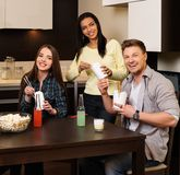 Amis mangeant des aliments de préparation rapide à la maison Photographie stock libre de droits