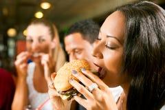 Amis mangeant des aliments de préparation rapide dans un restaurant Image libre de droits