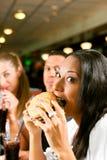 Amis mangeant des aliments de préparation rapide dans un restaurant Images libres de droits