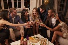 Amis mangeant des casse-croûte comme ils célèbrent à la partie ensemble Photos libres de droits