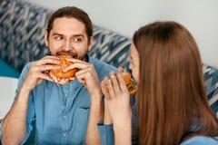 Amis mangeant des hamburgers à l'intérieur Photo libre de droits