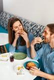 Amis mangeant des hamburgers à l'intérieur Photos stock