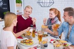 Amis mangeant des hamburgers Photographie stock libre de droits