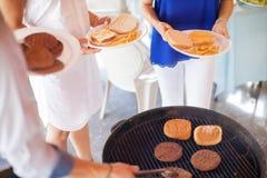 Amis mangeant des hamburgers dans un barbecue Photos stock