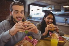 Amis mangeant des hamburgers en café Image stock