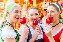 Amis mangeant des pommes de sucrerie chez Oktoberfest Image stock