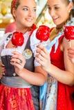 Amis mangeant des pommes de sucrerie chez Oktoberfest Photos stock