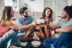 Amis mangeant du maïs éclaté et buvant la tasse de bière à la maison, ayant l'amusement Image libre de droits