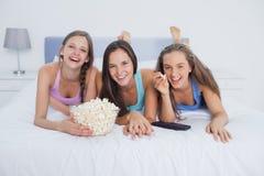 Amis mangeant du maïs éclaté et regardant la TV Images stock