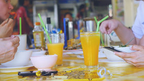 Amis mangeant en café thaïlandais prenant la photo sur la nourriture avec le téléphone portable dans eux voyageant Images stock