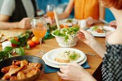 Amis mangeant ensemble à la maison Photo stock