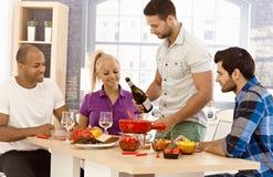 Amis mangeant ensemble à la maison Image stock