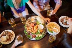 Amis mangeant et buvant à la barre ou au bar Photos libres de droits