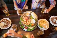 Amis mangeant et buvant à la barre ou au bar Photographie stock