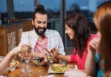 Amis mangeant et goûtant de la nourriture au restaurant Photos stock